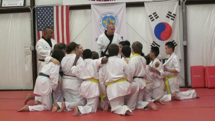 Taekwondo students huddling around their instructor