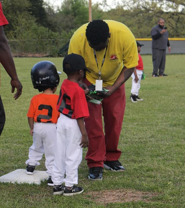 Coach assisting tee-ball player on the field
