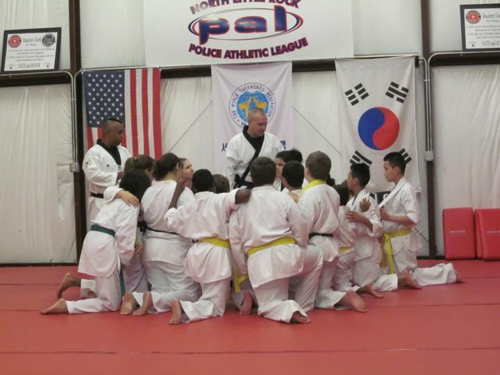 Kids at taekwondo practice huddling around their instructor